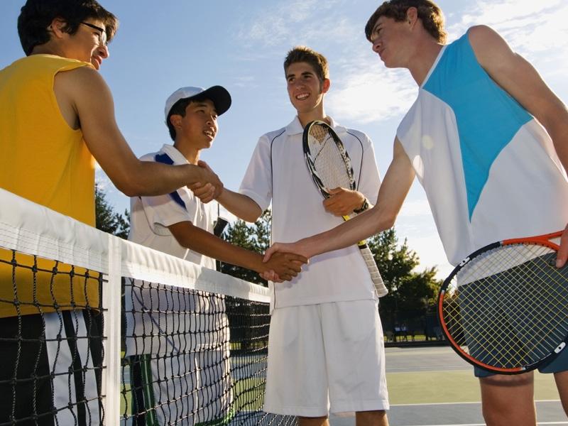 adolescents qui se serrent la main à la fin d'une partie de tennis