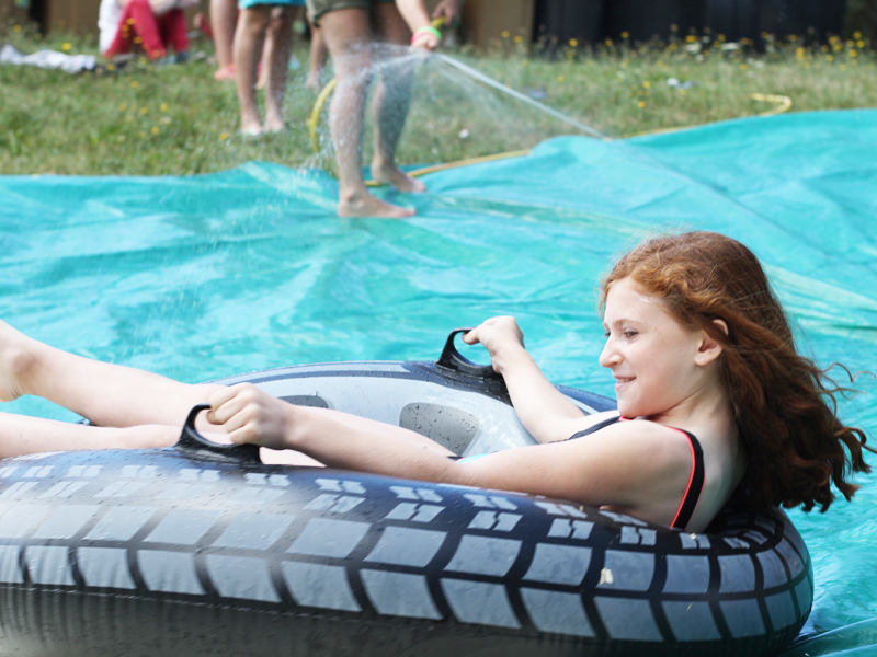 jeune ado jouant aux jeux d'eau sur une bouée en colo sportive