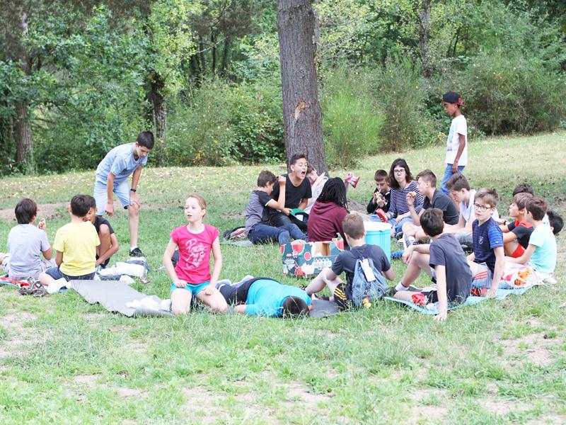 groupe d'enfants apprenant l'anglais en extérieur durant un stage sportif