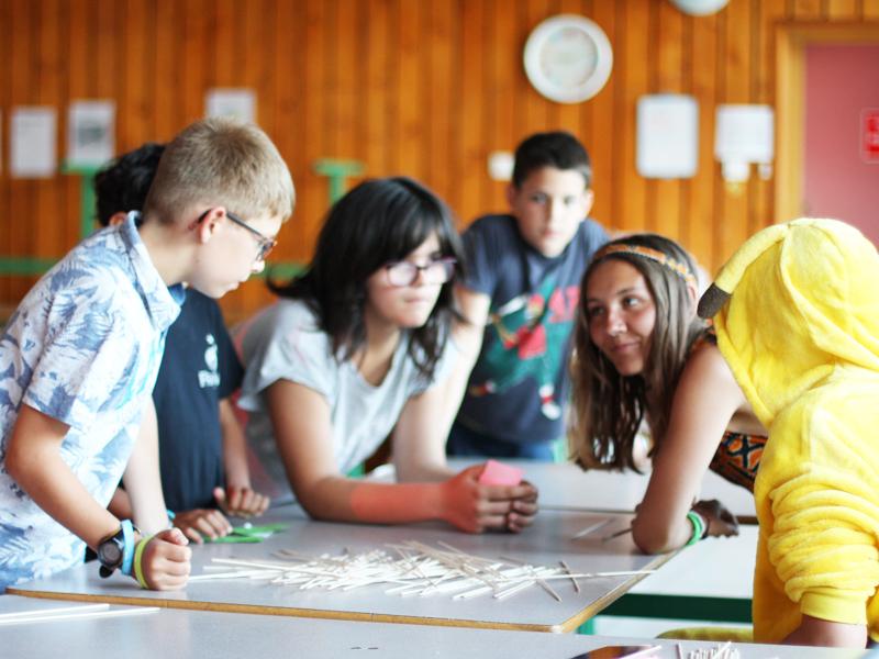 Enfants apprenant à parler anglais entre eux durant un stage sportif