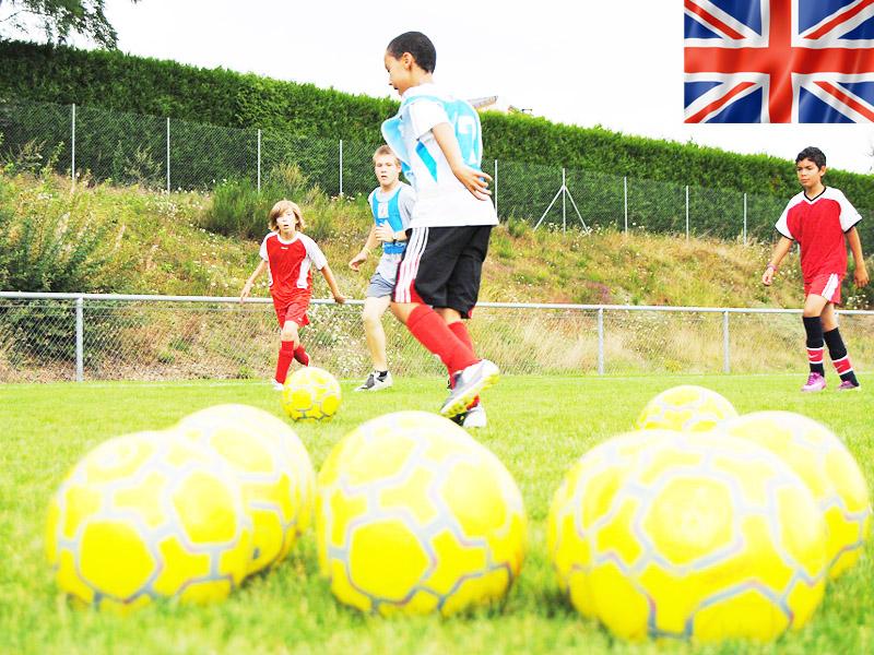 enfants et ados jouant au football durant un stage de football cet été
