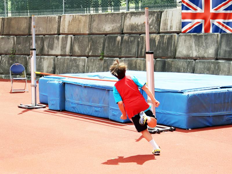 Enfant pratiquant le saut en hauteur en athlétisme cet été