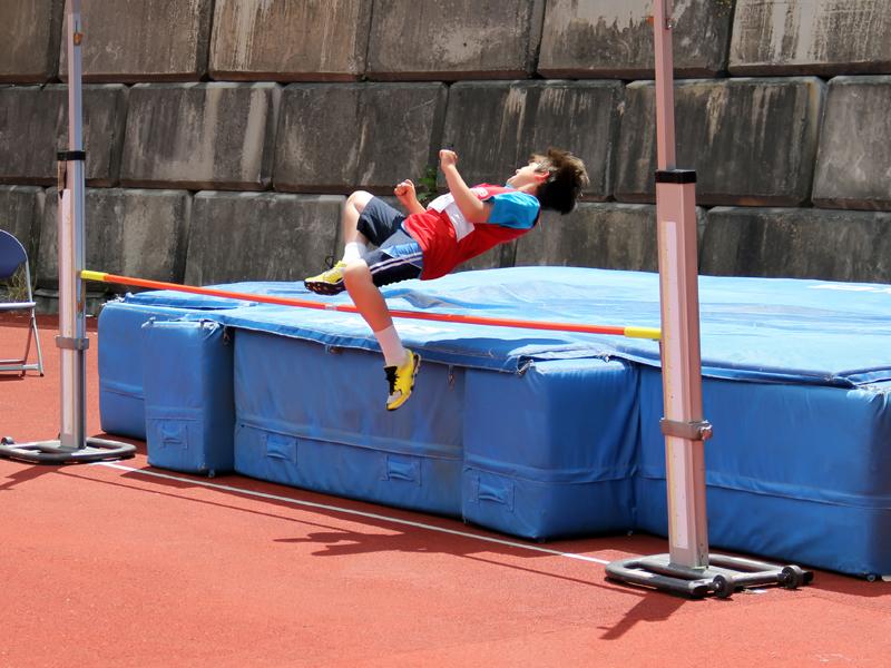 Enfant pratiquant le saut en hauteur en stage sportif cet été pour enfants et ados