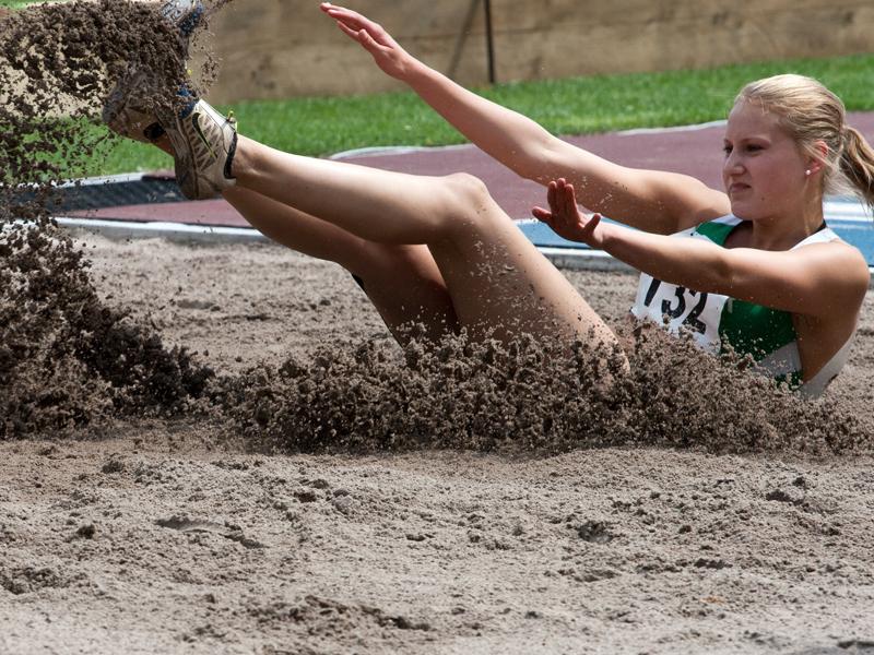 Jeune fille pratiquant le saut en longueur durant un stage athlétisme cet été