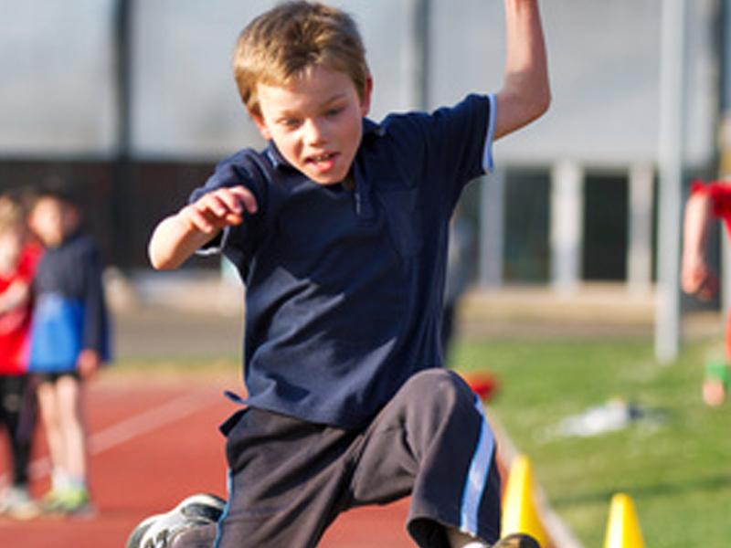 enfant en stage d'athlétisme faisant du saut de haie