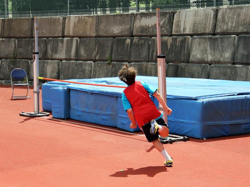 Enfant pratiquant le saut en hauteur en stage d'athlétisme cet été