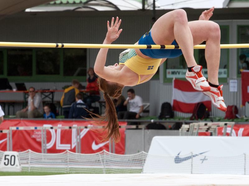 Adolescente pratiquant le saut en hauteur cet été durant un stage sportif athlétisme