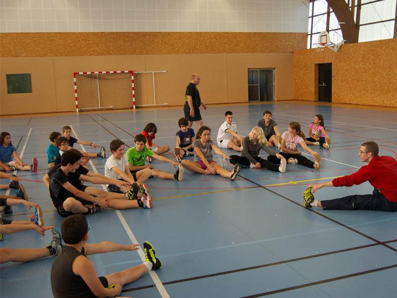 groupe d'enfants faisant des étirements avant un entrainement de badminton en stage sportif