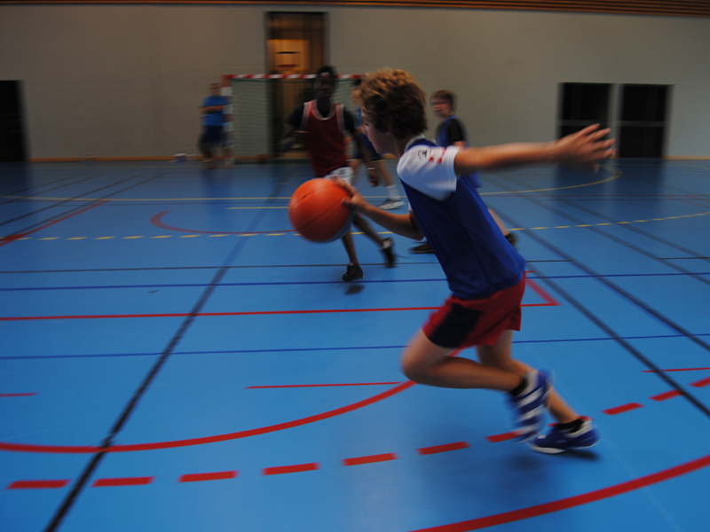 Enfant en train de jouer au basket durant un stage sportif de basketball
