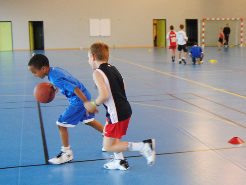 enfants jouant au basketball en colonie de stage sportif basket