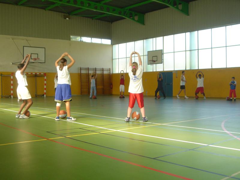 enfants jouant au basketball en intérieur en stage sportif d'été