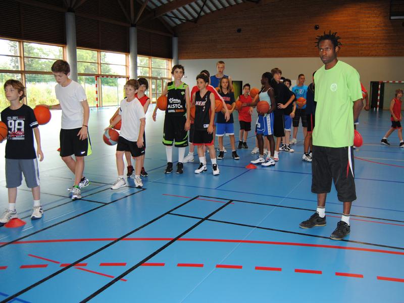 groupe d'enfants et ados en pleine partie de basketball cet été