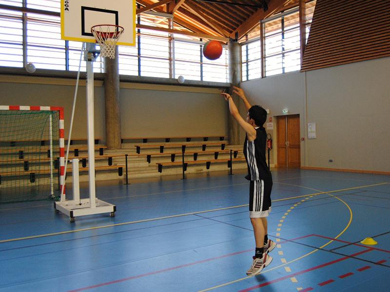 Adolescent jouant au basketball en été durant un stage sportif