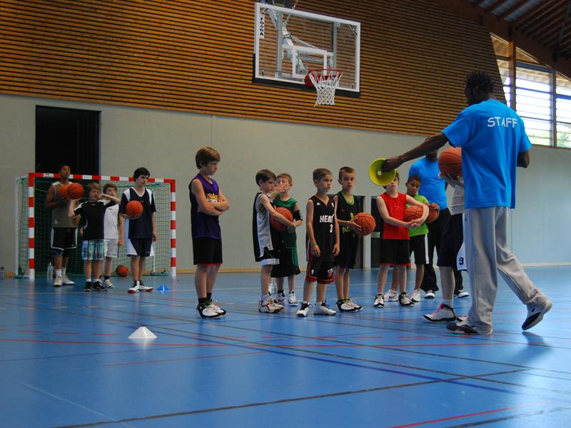 groupe d'enfants faisant du basketball en stage sportif