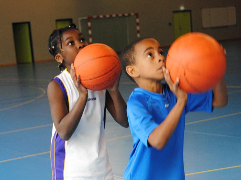 enfants s'entrainant à faire du basketball grace à un stage de basket