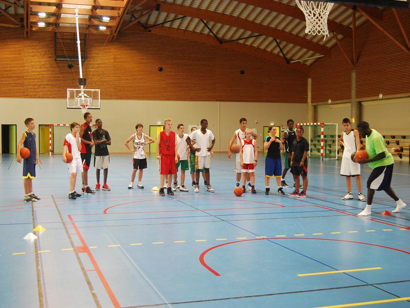 enfants et ados jouant au basketball en stage sportif cet été