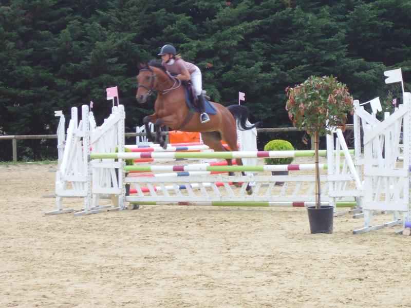 Adolescente pratiquant le saut d'obstacle en stage sportif d'équitation