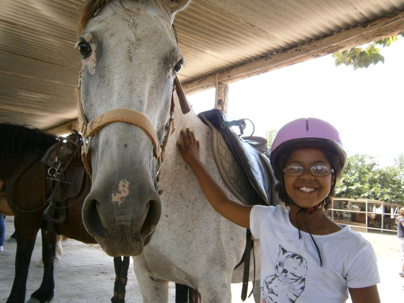 Portrait d'une enfant avec son cheval de stage sportif été