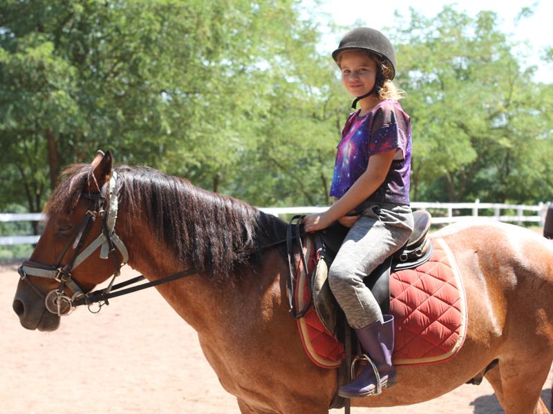 Ado sur un cheval en stage sportif d'équitation