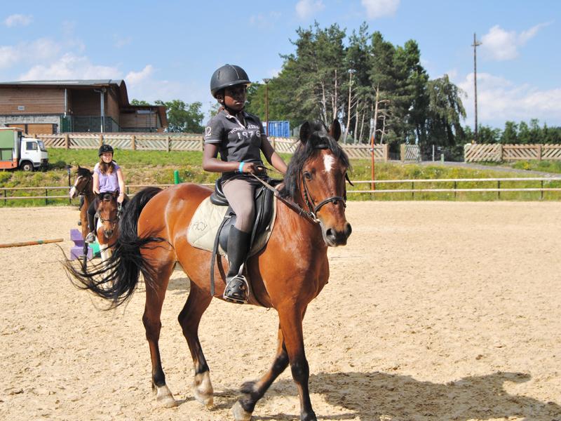 adolescente sur un cheval en stage sportif équitation été
