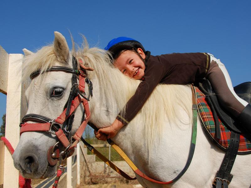 Enfant à dos de cheval en stage sportif équitation été