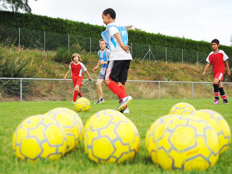 Enfants jouant au football cet été en stage sportif
