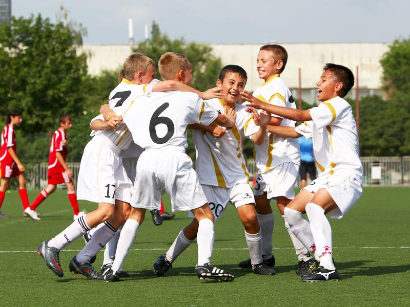 Groupe d'enfants heureux de faire du football en stage sportif de foot cet été