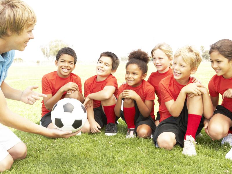Enfants apprenant à jouer au football avec un entraineur cet été en stage sportif
