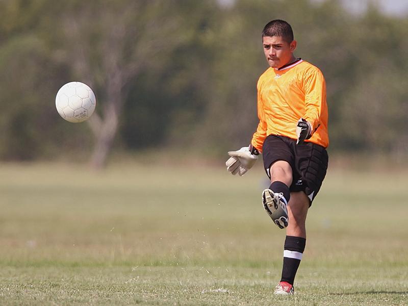 Adolescent s'entrainant au football cet été en stage sportif