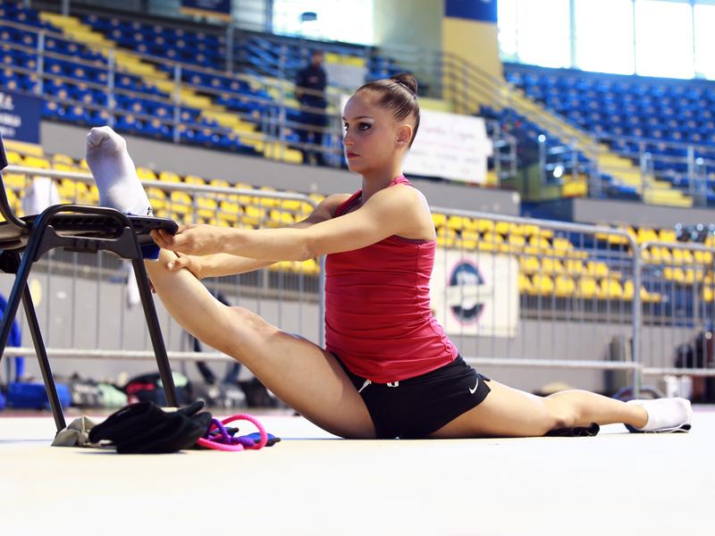 jeune fille faisant des étirements en stage sportif de gymnastique cet été