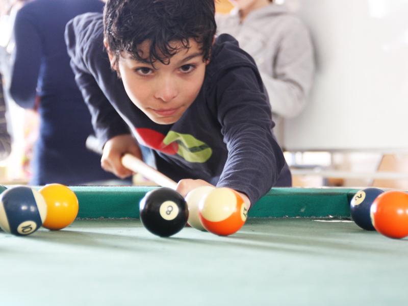 enfant jouant au billard pendant les temps libres de colonie de vacances cet été