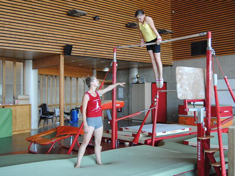 Jeune fille apprenant à faire des exercices à la barre en colonie de vacances gymnastique