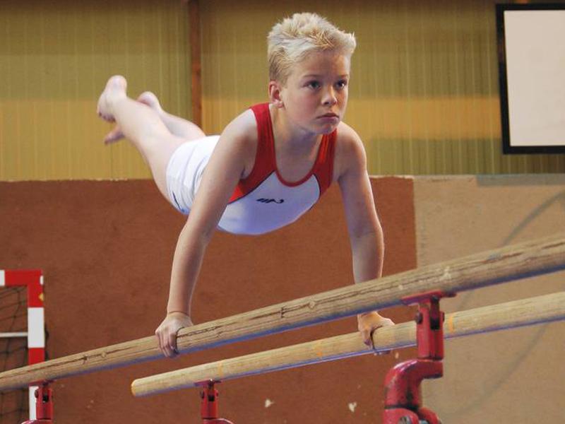 Jeune garçon faisant des barres parallèles en gymnastique artistique cet été