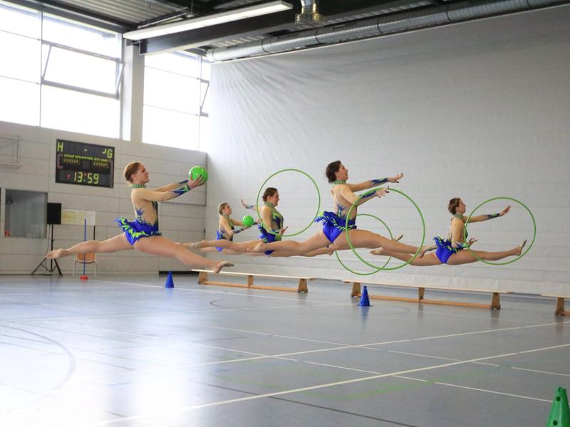 Adolescents faisant des sauts à cerceaux en colonie de vacances sportive