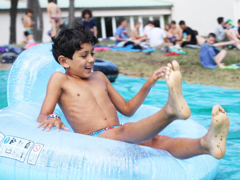 enfant faisant des glissades sur un jeu d'eau en colonie de vacances sportive cet été