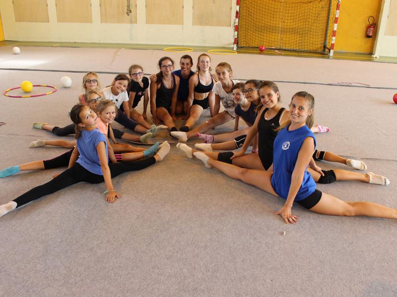 Groupe d'enfants faisant de la gymnastique au sol cet été