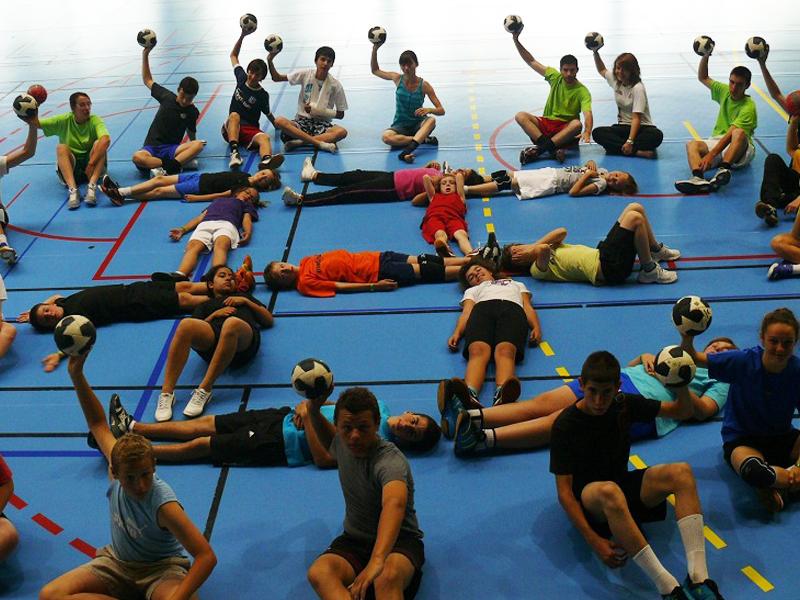 ados et enfants faisant des jeux de handball durant un stage sportif de handball cet été