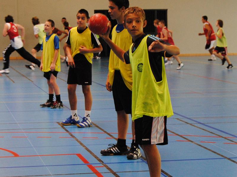 Enfants jouant au handball en stage sportif cet été