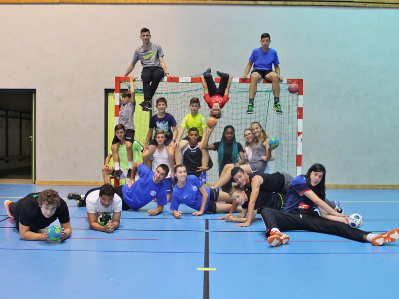 groupe d'enfants et ados jouant au handball en stage sportif cet été