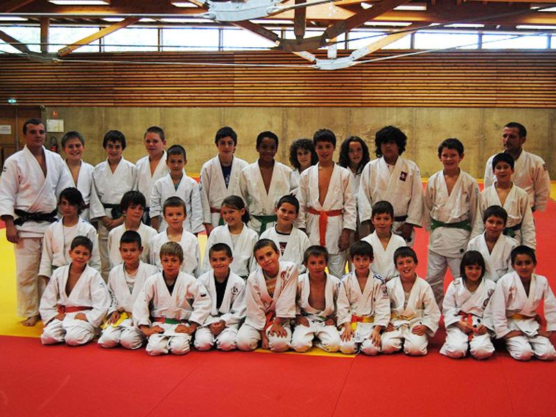 Groupe d'ados et enfants faisant du judo en stage sportif été