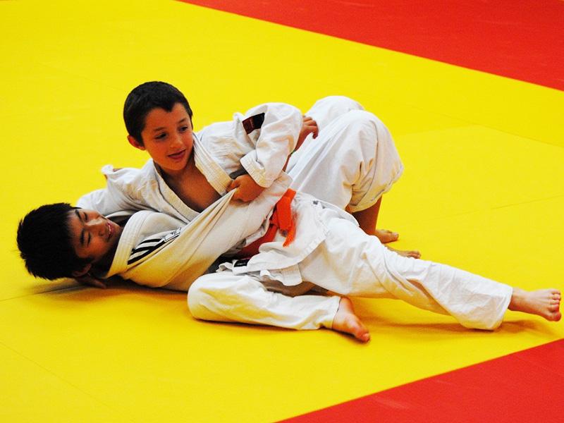 Enfants faisant du judo cet été en stage sportif