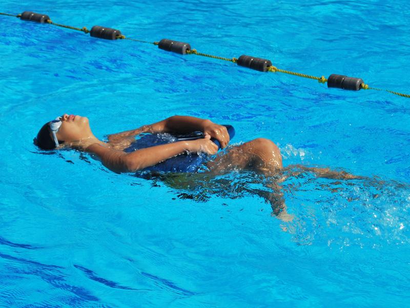 Enfant apprenant différentes techniques de nage en stage sportif d'été natation
