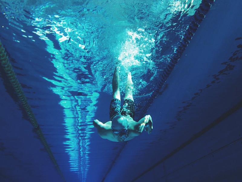 Ado apprenant la plongée en piscine durant un stage sportif de natation été