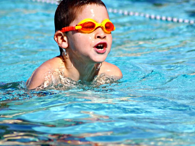 Enfant à la piscine avec des lunettes de plongée en stage sportif de natation cet été