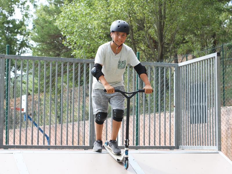 Adolescent faisant du skateboard et roller en colonie de vacances d'été
