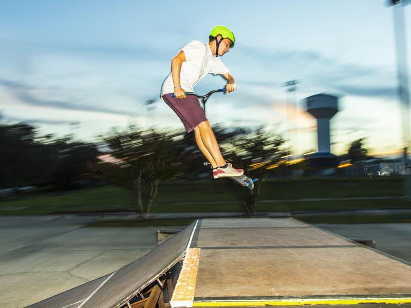 Adolescent pratiquant le saut à trottinette en stage sportif d'été