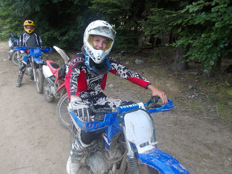 groupe d'ados faisant de la moto dans les bois en stage sportif cet été