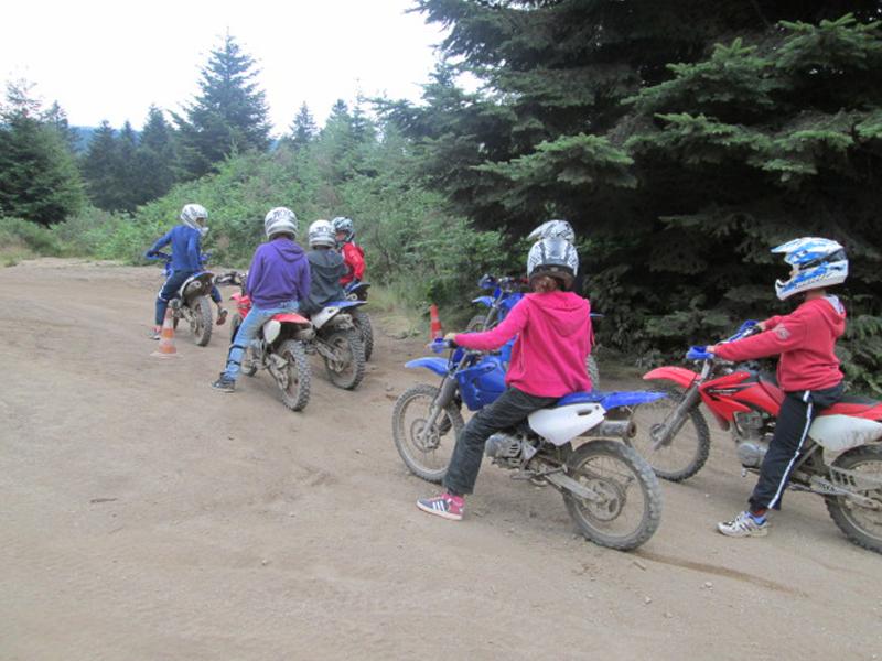 Enfants apprenant à faire de la moto cross cet été en colonie de vacances