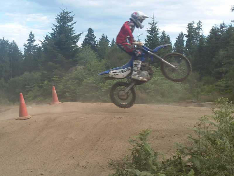 adolescent faisant de la moto à haut niveau en stage sportif de moto cross cet été