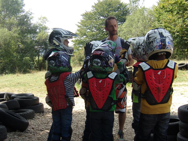 enfants et leur animateur de colonie de vacances apprenant à s'équiper pour faire de la moto en colo